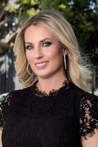 Head shot of Christy Lewis - white woman with blonde hair wearing a black lace top